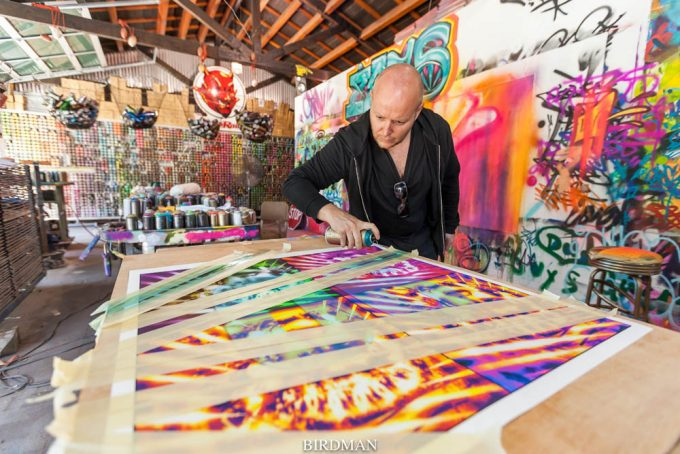Lincoln Townley at the studio of Los Angeles Street artist Risk Rock creating a custom embellished print of his Queen at 90 portrait