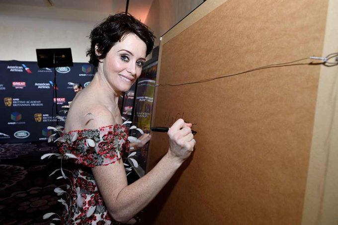 Actor Claire Foy signing her portrait by British artist Lincoln Townley