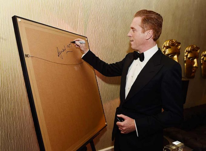 Actor Damian Lewis seen here signing his portrait by British artist Lincoln Townley