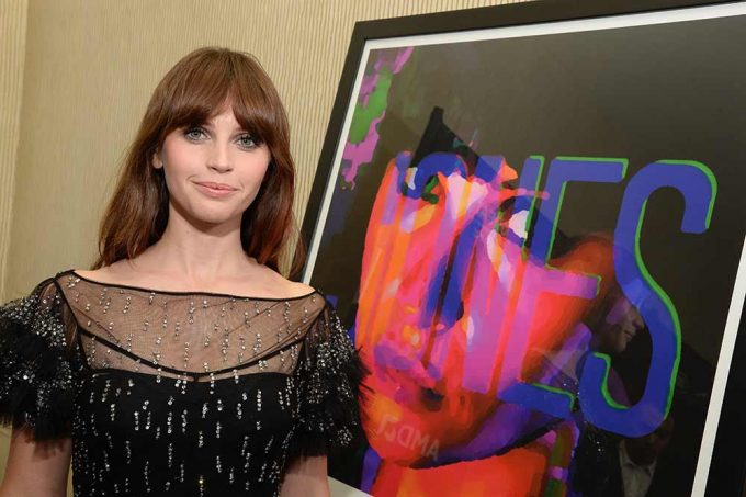 Actor Felicity Jones stands with her abstract portrait created by British artist Lincoln Townley