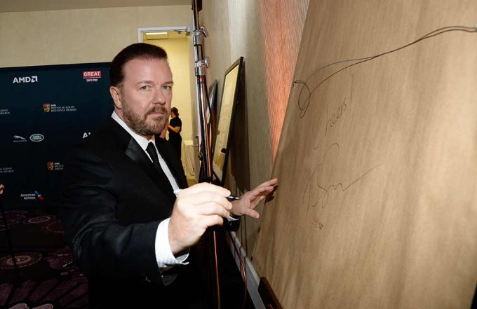 Comedy legend Ricky Gervais signing his portrait created by British artist Lincoln Townley