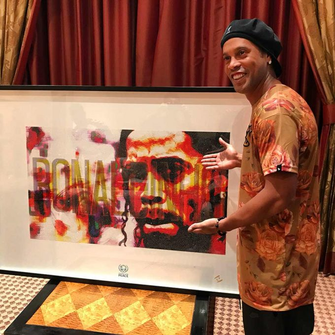 Football Icon Ronaldinho with his portrait created by British artist Lincoln Townley
