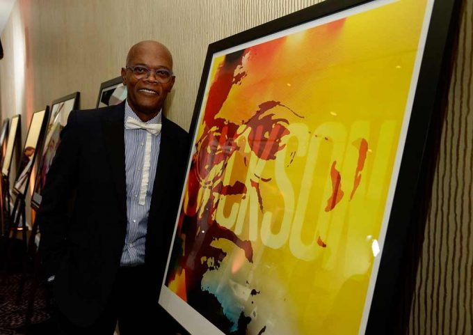 Actor Samuel L Jackson standing next to his portrait created by British artist Lincoln Townley