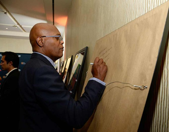 Actor Samuel L Jackson signing his portrait created by British artist Lincoln Townley